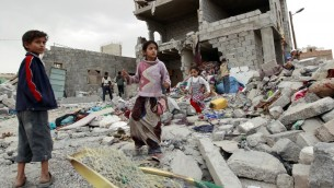 اطفال يمنيون يقفون وسط حطام منزل دمر اثر غارات التحالف العربي في صنعاء، 13 يوليو 2015 (MOHAMMED HUWAIS / AFP)