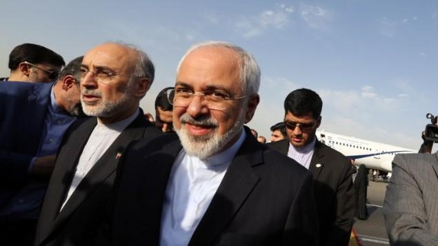 وزير الخارجية الإيراني محمد جواد ظريف ورئيس منظمة الطاقة النووية الإيرانية علي اكبار صالحي في مطار في طهران، 15 يوليو 2015 (AFP/ATTA KENARE)