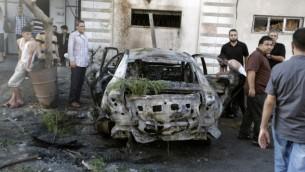 فلسطينيون يحتشدون حول سيارة محترقة في مدينة غزة في 19 يوليو، 2015، بعد أن دمرت سلسلة من الإنفجارات 5 مركبات في غزة تابعة لأعضاء في حركتي حماس والجهاد الإسلامي، بحسب شهود عيان ومصادر أمنية، في خضم توترات بين حكام القطاع الفلسطيني ومتطرفين إسلاميين. (AFP/MOHAMMED ABED)
