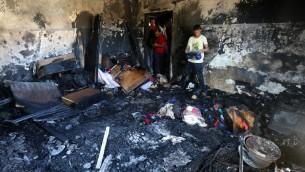 فلسطينيون يتفحصون الدمار في منزل عائلة دوابشة، حيث قتل رضيع بهجوم حريق نفذه ارهابيين يهود في بلدة دوما في الضفة الغربية، 31 يوليو 2015 (AFP/Jaafar Ashtiyeh)