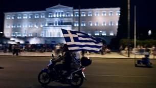 سائق دراجة نارية مع مسافر معه يحملان العلم اليوناني أمام البرلمان اليوناني في 5 يوليو، 2015، بعد أن توقعت النتائج الأولية فوز أولئك الذين رفضوا المزيد من إجراءات التقشف في إستفتاء شعبي حاسم. (AFP/ARIS MESSINIS)
