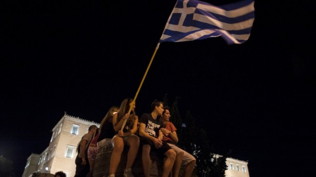 شابة يونانية تحمل العلم اليوناني وسط إحتفالات أمام البرلمان في 5 يوليو، 2015 في أثينا بعد أن توقعت النتائج الأولية فوز أولئك الذين رفضوا المزيد من إجراءات التقشف في إستفتاء شعبي حاسم.(AFP PHOTO /IAKOVOS HATZISTAVROU)
