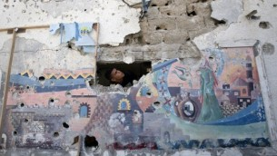 رجل فلسطيني يتفقد الأضرار التي لحقت بمدرسة تابعة للأمم المتحدة في مخيم جباليا للاجئين شمال قطاع غزة ، 30 يوليو، 2014. (AFP/Mahmud Hams)