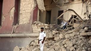 شرطي مصري يقف بين الحطام في مكان انفجار سيارة مفخخة هدمت اقسام من مقر القنصلة الإيطالية في القاهرة، 11 يوليو 2015 (MOHAMED EL-SHAHED / AFP)