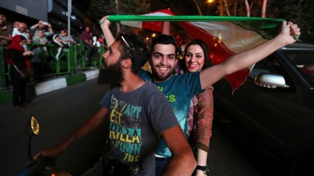 إيرانيون يلوحون بعلمهم في طهران خلال الاحتفال بتوقيع الاتفاق النووي، 14 يوليو 2015 (ATTA KENARE / AFP)