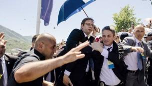 رئيس الوزراء الصربي الكسندر فوسيتش تحت حماية حراسه اثناء رشقه بالحجارة خلال مراسم الذكرى السنوية العشرين لضحايا سريبرينيتسا في البوسنة، 11 يوليو 2015 (DIMITAR DILKOFF / AFP)
