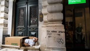 رجل من دون مأوى ينام في صندوق كرتوتي خارج محل تجاري مغلق في وسط أثينا، 5 يوليو، 2015. (PHOTO / ANDREAS SOLARO)