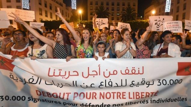 مغاربة يطلقون هتافات ويحملون لافتات خلال تظاهرة في الرباط ضد إعتقال فتاتين مغربيتين بسبب إرتداء تنورة، 6 يوليو، 2015. (AFP/FADEL SENNA)