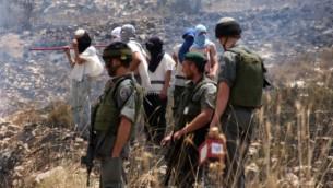 مستوطنون ملثمون بجانب جنود اسرائيليين في الضفة الغربية (Wagdi Ashtiyeh/Flash90)