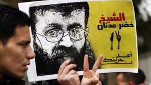 شاب قلسطيني يحمل صورة للأسير الفلسطيني خضر عدنان في تظاهرة إحتجاجا على الإعتقال الإداري السابق لعدنان، 10 فبراير، 2012.