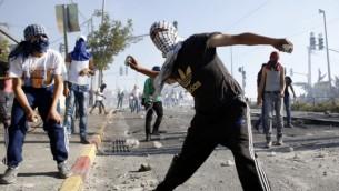 صورة توضيحية: شبان فلسطينيون يلقون الحجارة على الشرطة الإسرائيلية خلال مواجهات في القدس الشرقية، 4 يوليو، 2014. (Sliman Khader/Flash90)