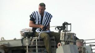جندي اسرائيلي يصلي فوق مركبة عسكرية مدرعة بالقرب من الحدود مع غزة في أول يوم في عملية الجرف الصامد، 8 يوليو 2014 (David Buimovitch/Flash90)