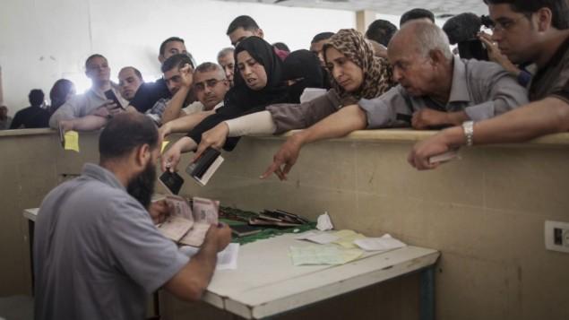 فلسطينيون يحتشدون عند معبر رفح الحدودي جنوب قطاع غزة، خلال إنتظارهم الحصول على تصريحات لدخول مصر في 12 يونيو، 2015. (Flash90/Aaed Tayeh)