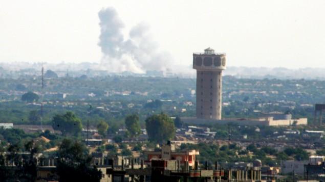"""تصاعد الدخان في شمال سيناء، كما يظهر من الحدود مع قطاع غزة، في خضم إشتباكات عنيفة بين قوات الحكومة ومسلحين تابعين لتنظيم """"الدولة الإسلامية"""" في 1 يوليو، 2015. (Abed Rahim Khatib/Flash90)"""