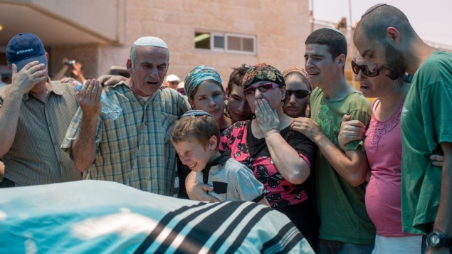 عائلة مالاخي موشيه روزنفيلد تبكي إبنها خلال جنازته في كوخاف هشاحر في الضفة الغربية، 1 يوليو، 2015. (Yonatan Sindel/Flash90)