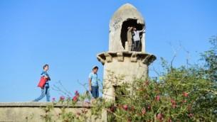 """إسرائيليون يقفون فوق سطح مبنى في ما كانت في السابق مستوطنة """"سانور""""، إحدى المستوطنات الأربعة التي تم إخلاؤها من سكانها اليهود ضمن خطة فك الإرتباط عام 2005، 21 يوليو، 2015. (Flash90)"""