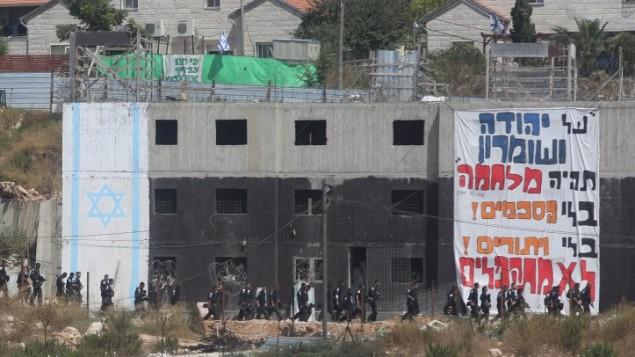 قوات الأمن الإسرائيلية تمر بجانب مبنى تحصن فيه مستوطنين لمحاربة اخلائه في مستوطنة بيت ايل في الضفة الغربية، 28 يوليو 2015 (Flash90)