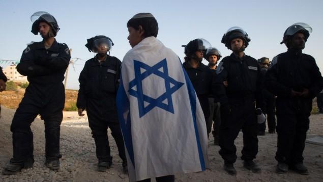"""فتى يهودي يلف نفسه بالعلم الإسرائيلي يقف بالقرب من قوات الأمن الإسرائيلية التي جاءت إلى إخلاء مبان غير قانونية في مستوطنة """"بيت إيل""""،  28 يوليو، 2015. (Nati Shohat/FLASH90)"""