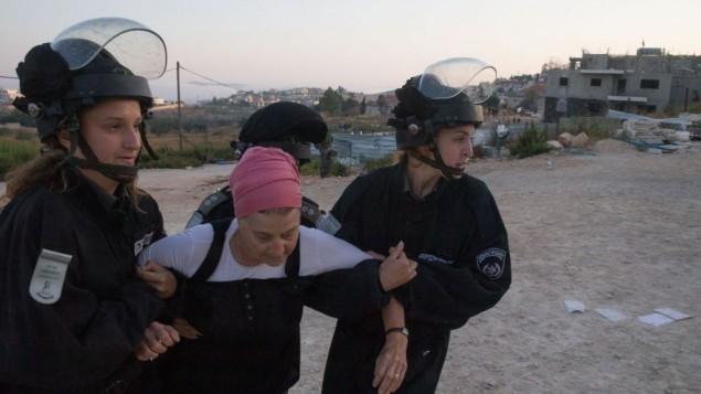 """قوات الأمن الإسرائيلية تقوم بإبعاد مستوطنة يهودية جاءت للإحتجاج على عملية إخلاء في مستوطنة """"بيت إيل""""، بالقرب من مدينة رام الله في الضفة الغربية، 28 يوليو، 2015. (Nati Shohat/FLASH90)"""