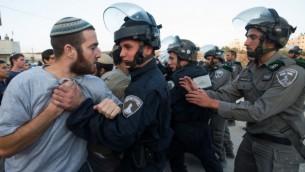 """مواجهات بين قوات الأمن الإسرائيلية والمستوطنين الذين تحصنوا في مبان في محاولة منهم لمنع هدم مبان تم بناؤها بصورة غير قانونية، في مستوطنة """"بيت إيل"""" بالقرب من مدينة رام الله في الضفة الغربية، 28 يوليو، 2015. (Nati Shohat/FLASH90)"""