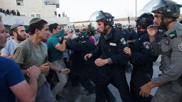 قوات الأمن الإسرائيلية تتشابك مع مستوطنين تحصنوا داخل مبنى بمحاولة لمنع اخلائه في مستوطنة بيت ايل في الضفة الغربية، 28 يوليو 2015 (Nati Shohat/FLASH90)