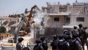 """قوات الأمن تراقب بينما تقوم جرافة بهدم مبنيين في مستوطنة """"بيت إيل"""" الإسرائيلية، بالقرب من مدينة رام الله في الضفة الغربية، 29 يوليو، 2015. (Yonatan Sindel/FLASH90)"""