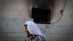 رجل فلسطيني يمر امام منزل عائلة دوابشة في بلدة دوما في الضفة الغربية، حيث أدى هجوم حريق من قبل إرهابيين يهود الى مقتل رضيع فلسطيني عمره 18 شهرا، 31 يوليو 2015 (FLASH90)