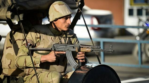 جندي مصري خارج المطار العسكري المزة حيث اقلعت جثامين الجنود الذين قتلوا في محافظة شمال سيناء خلال هجوم في اليوم السابق، 30 يناير 2015 (AFP/ Mohamed el-Shahed)