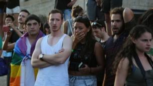 المشاركون في موكب الفخر المثلي في القدس ينظرون بانصدام بينما تعالج طواقم الإسعاف ضحايا هجوم الطعن، 30 يوليو 2015 (Eric Cortellessa/Times of Israel)
