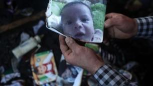 رجل يعرض صورة الرضيع الفلسطيني على سعد دوابشة البالغ من العمر 18 شهرا، والذي قُتل بعد إحراق منزل عائلته على يد متطرفين يهود في قرية دوما في الضفة الغربية،  31 يوليو، 2015. (AFP/Jaafar Ashtiyeh)