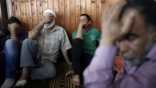 اقرباء الرضيع الفلسطيني علي دوابشة، يحدون بالقرب من جثمانه داخل مسجد خلال تشييع جثمانه في بلدة دوما في الضفة الغربية، 31 يوليو 2015 (AFP PHOTO / THOMAS COEX)