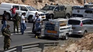 صورة توضيحية للشرطة تتفحص موقع هجوم اطلاق نار استهدف مركبة اسرائيلية في طريق بالقرب من مستوطنة كوخاف هاشاحار في الضفة الغربية، 31 يوليو 2015 (AFP PHOTO/THOMAS COEX)
