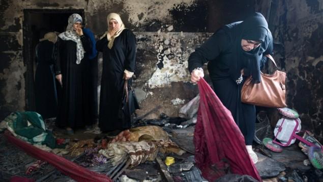 نساء فلسطينيات يتفحصن حطام منزل عائلة دوابشة في بلدة دوما في الضفة الغربية، 4 اغسطس 2015 (MENAHEM KAHANA / AFP)