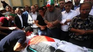 رجال فلسطينيون يصلون على جثمان سعد دوابشة، والد الرضيع الفلسطيني الذي قُتل في الأسبوع الماضي بعد أن قام متطرفون يهود بإشعال النار في  منزله، خلال جنازته في قرية دوما غب الضفة الغربية، 8 أغسطس، 2015. (AFP/ JAAFAR ASHTIYEH)
