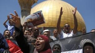 متظاهرون فلسطينيون يهنفون شعارات خلال تظاهرة أمام قبة الصخرة  في المسجد الأقصى  بالبلدة القديمة في القدس.، 14 أغسطس، 2015، تضامنا مع محمد علان، الأسير الفلسطيني الذي تحتجزه إسرائيل من دون محاكمة والذي دخل في حالة غيبوبة بعد حوالي شهرين من إضرابه عن الطعام. (AFP PHOTO/AHMAD GHARABLI)