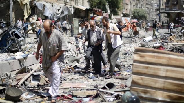 سوريون يسيرون وسط الأنقاض في أعقاب غارات جوية نفذتها طائرات النظام السوري على سوق في منطقة دوما التي يسيطر عليها المتمردون، شرقي العاصمة دمشق، 16 أغسطس، 2015. (Sammer al Doumy/AFP)