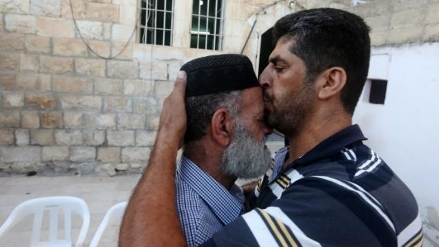 رجل فلسطيني يهنىء ويقبل جبين ناصر الدين علان، والد السجين محمد علان ، بعد أنباء  بشأن تعليق احتجازه، الصورة في منزل العائلة في مدينة نابلس بالضفة الغربية  19 آب،  2015. AFP PHOTO / JAAFAR ASHTIYEH