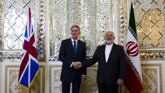 وزير الخارجية الايراني محمد جواد ظريف (R) يصافح نظيره البريطاني فيليب هاموند قبل مؤتمرهم الصحفي المشترك في طهران 23 أغسطس، حيث فتح وزير الخارجية 2015.السفارة البريطانية في طهران   AFP PHOTO/BEHROUZ MEHRI