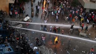 """متظاهرون لبنانيون يهتفون شعارات بينما شرطة مكافحة الشغب ترشهم بخراطيم المياه في مظاهرة نظمتها حملة """"طلعت ريحتكم"""" في وسط بيروت، 23 اغسطس 2015 (AFP)"""