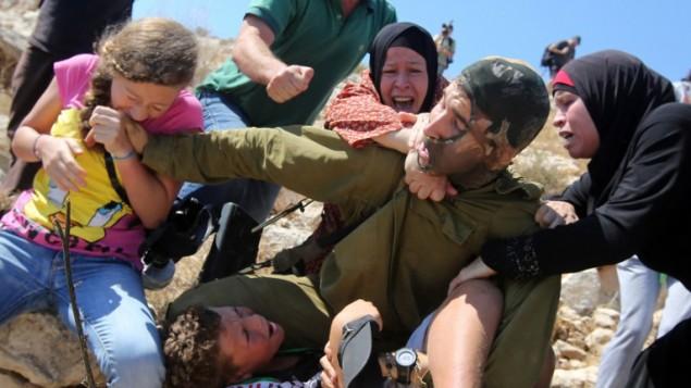 فلسطينيات يحاولن عرقلة محاولة جندي اسرائيلي لاعتقال طفل فلسطيني في بلدة النبي صالح في الضفة الغربية، 28 اغسطس 2015 (AFP/ABBAS MOMANI)