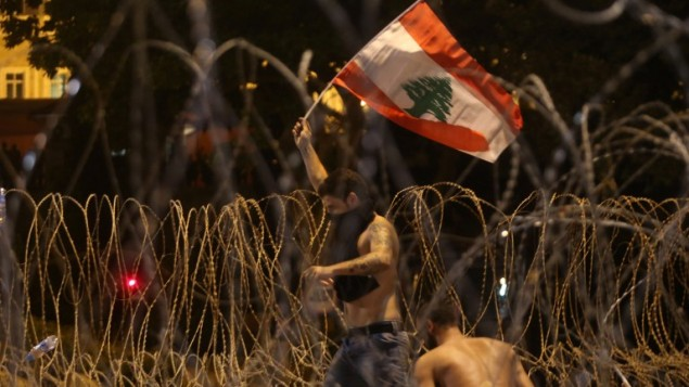 رجل لبناني يلوح بالعلم اللبناني بينما يحاول إجتياز الإسلاك الشائكة التي تفصل المحتجين عن السراي الحكومي خلال تظاهرة حاشدة ضد الطبقة الحاكمة التي يُنظر إليها بأنها فاسدة وغير قادرة على توفير الخدمات الأساسية، 29 أغسطس، 2015 في ساحة الشهداء في بيروت. (AFP PHOTO / STR)