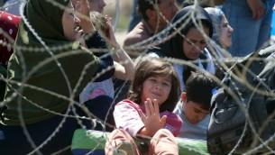 المهاجرون في انتظار الشرطة المكدونية للسماح لهم بدخول مكدونيا على الحدود بين اليونان ومقدونيا بالقرب من مدينة غيفغليا في 28 أغسطس، 2015. (AFP PHOTO / ROBERT ATANASOVSKI)