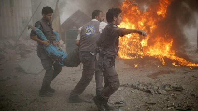 طواقم انقاذ سورية تحمل رجل مصاب بغارة النظام السوري على سوق مدنية مزدحمة في بلدة دوما الخاضعة لقوات المعارضة، 16 اغسطس 2015 (SAMEER AL-DOUMY / AFP)