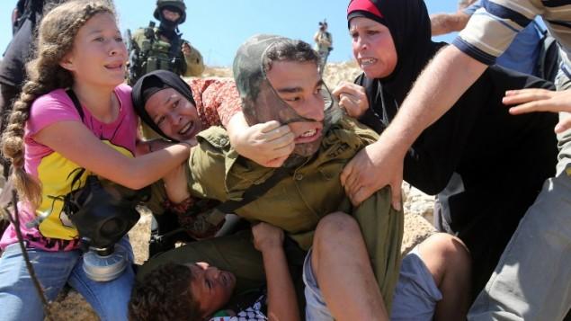 فلسطينيات يحاولن عرقلة محاولة جندي اسرائيلي لاعتقال طفل فلسطيني في بلدة النبي صالح في الضفة الغربية، 28 اغسطس 2015 (AFP Photo/Abbas Momani)