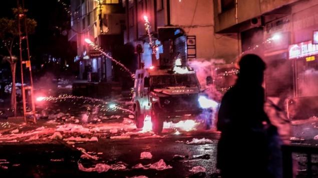 مسلحون يلقون مفرقعات بإتجاه مركبة مدرعة تابعة للشرطة خلال اشتباكات مع الشرطة التركية في 27 أغسطس، 2015 في حي غازي في إسطنيول.  (AFP PHOTO/OZAN KOSE)