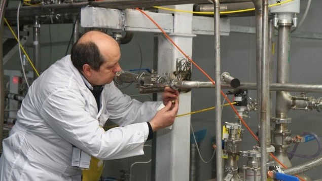 مفتش الوكالة الدولية للطاقة الذرية يقوم بقطع الإتصالات بين أجهزة الطرد المركزي لإنتاح اليورانيوم بنسبة 20% في مفاعل ناتانز النووي جنوب طهران في 20 يناير، 2014. ( Kazem Ghane/IRNA/AFP)