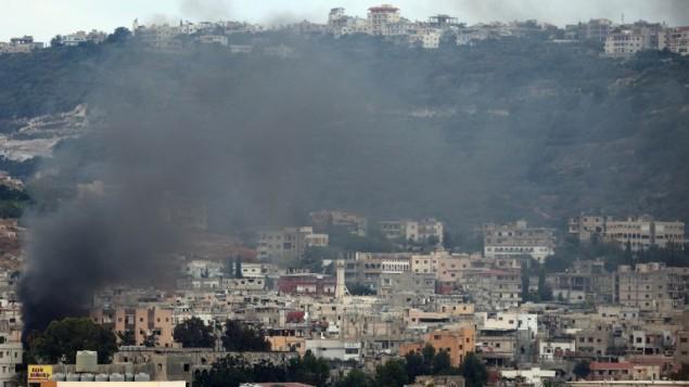 الدخان يتصاعد من مخيم عين الحلوة للاجئين الفلسطينيين القريب من مدينة صيدا الساحلية جنوب لبنان خلال  إشتباكات في 25 أغسطس، 2015. (Mahmoud Zayyat/ AFP)