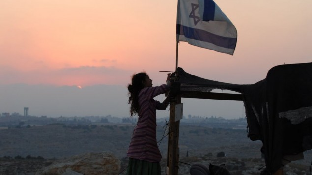 """طفلة إسرائيلية ترفع العلم الإسرائيلي فوق مبنى مؤقت في بؤرة """"غيفعات تسوريا"""" الإستيطانية بالقرب من مستوطنة """"أفني حيفيتس""""، التي تقع شرقي مدينة طولكرم الفلسطينية، في صورة من عام 2009. (Gili Yaari / FLASH90)"""