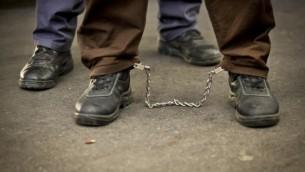 أسير فلسطيني مع أصفاد في رجليه في إسرائيل (Moshe Shai/Flash90)