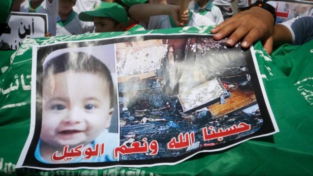 اطفال فلسطينيون يحملون نعش عليه صورة علي سعد دوابشة، 18 شهرا، الرضيع الذي قتل حرقا في الهجوم في بلدة دوما خلال مظاهرة في خان يونس في قطاع غزة، 1 اغسطس 2015 (Rahim Khatib / Flash 90)